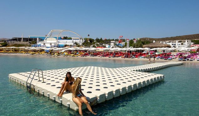 women sitting on sunny pier